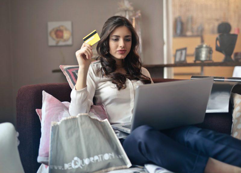 Femeie ţine un card în mână şi cumpără din magazinele online